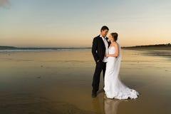 Jonggehuwden op een verlaten strand bij zonsondergang Stock Foto's