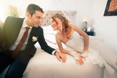 Jonggehuwden in slaapkamer loving royalty-vrije stock afbeeldingen