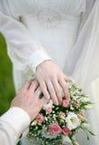 Jonggehuwdenhanden en een boeket van bloemen Royalty-vrije Stock Foto's