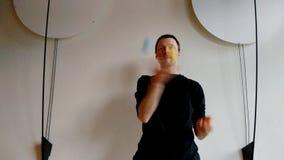 Jonglör med tre färgbollar för den vita väggen med garnering på sidor stock video