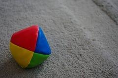 Jonglera bollen på grå färgmatta fotografering för bildbyråer