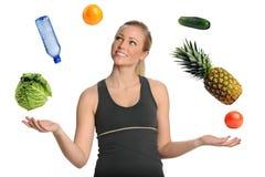 Jonglera fruktgrönsaker och vatten för kvinna Arkivbild