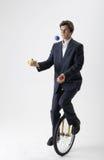 Jonglierender Geschäftsmann auf Unicycle Stockfotos