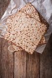 Joodse kosjer matzahclose-up op papier op een lijst verticale bovenkant v Royalty-vrije Stock Afbeeldingen