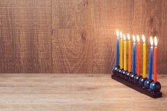 Joodse Vakantiechanoeka menorah met kleurrijke kaarsen over houten achtergrond Stock Fotografie