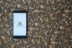 Joomla-Logo auf Smartphone auf Hintergrund von kleinen Steinen Stockfotos