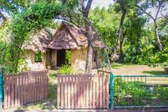 Jord- hus under skugga av träd Ett jordhus, också som var bekant som jordbermen, jord beskyddade hem, eller eco-huset är en archi Royaltyfri Bild