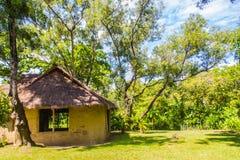Jord- hus under skugga av träd Ett jordhus, också som var bekant som jordbermen, jord beskyddade hem, eller eco-huset är en archi Arkivbilder
