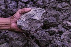 Jord i bondemanhänder av svart jordbakgrund Jord är en blandning Royaltyfri Bild