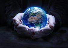 Jord i händer - begrepp för miljöskydd Arkivbild