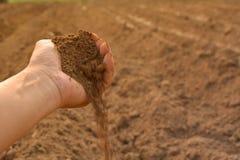 Jord i kultiverad smuts för hand jord eller jordning med naturbackg Arkivbilder