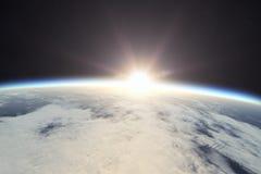 Jord med soluppgång i utrymme Arkivbild