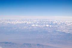Jord och blå himmel, flyg- sikt stora liggandebergberg Miljöskydd och ekologi reslust och lopp Jord är Royaltyfri Bild