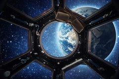 Jord och galax i rymdskeppinternationella rymdstationenfönster arkivbild