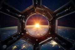 Jord och galax i rymdskeppinternationella rymdstationenfönster Royaltyfri Bild