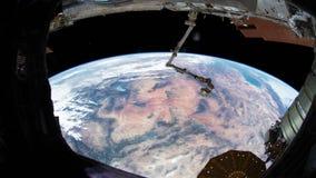 Jord som sett igenom fönster av internationella rymdstationen ISS Beståndsdelar av denna avbildar möblerat av NASA arkivfilmer