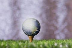 Jorda en kontakt att klibba med golfbollen på en utslagsplatspinne Arkivfoto