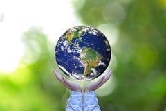 jorda en kontakt glödande händer för jordklotet hans holding Arkivfoton