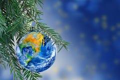 Jorda en kontakt jordklotet som en julstruntsak på granfilialen, kopieringsutrymme Arkivfoto