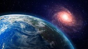 Jorda en kontakt och en spiralgalax i bakgrunden Arkivfoto