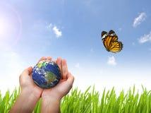 Jorda en kontakt planeten och fjärilen i kvinnlig hand på blå himmel Royaltyfri Fotografi