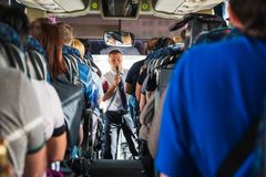Tourists and a male tour guide with a microphone in the bus. Jordan, Akaba - December 19, 2017: Tourists and a male tour guide with a microphone in the bus royalty free stock photography
