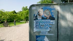 Jordan Bardella and Marine Le Pen Rassemblement National. Strasbourg, France - May 23, 2019: Damaged Posters in green sunny park for 2019 European Parliament stock video