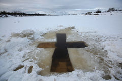 Jordan for the Epiphany bathing near Pskov, Russia. Cross-shaped ice hole called the Jordan for the Epiphany bathing in the Velikaya River at the Vybuty Pogost Royalty Free Stock Photo