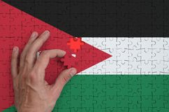 Jordan flag is depicted on a puzzle, which the man`s hand completes to fold.  royalty free illustration