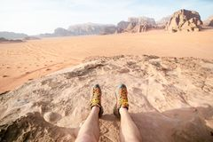 Jordan national park Wadi Rum desert. Beautiful view and panoramatic picture of man legs and outdoor shoes. Natural background. Su. Nset in a desert royalty free stock images