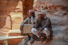 Jordan Petra Arab Bedouin People. Picture of 2 arab man in the beautiful Petra, Jordan. Both dressed in a jalabiyyeh, bedouin style clothes stock images
