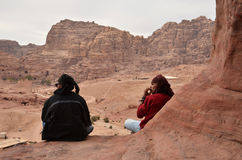 Jordan, Petra. Two men- Bedouin sit on edge of a cliff Royalty Free Stock Photos