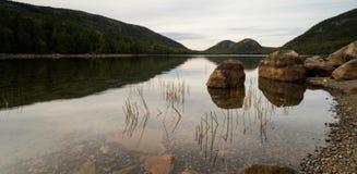 Jordan Pond med vaggar och reflexioner och den gröna skogen royaltyfria foton