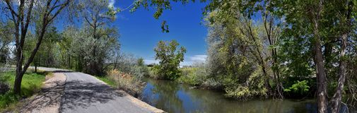 Jordan River Parkway Trail, Redwood Trailhead bordering the Legacy Parkway Trail, panorama views with surrounding trees and silt f. Illed muddy water along the royalty free stock photography