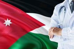 Jordanian Arts die zich met stethoscoop op de vlagachtergrond van Jordanië bevinden Het nationale concept van het gezondheidszorg royalty-vrije stock foto's