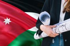 Jordanian de holdingsblauwdruk van de Architectenvrouw tegen golvende de vlagachtergrond van Jordanië Bouw en architectuurconcept stock afbeeldingen