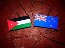 Jordanian flag with New Zealand flag on a tree stump isolated. Jordanian flag with New Zealand flag on a tree stump stock illustration