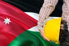 Jordanian Ingenieur houdt gele veiligheidshelm met golvende de vlagachtergrond van Jordanië Bouw en de bouwconcept royalty-vrije stock fotografie
