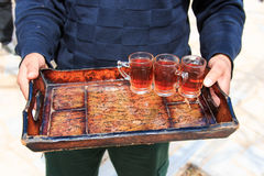 Jordanian man offering tea to the tourists visiting a local house.  Royalty Free Stock Photography