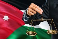 Jordanian Rechter houdt gouden schalen van rechtvaardigheid met golvende de vlagachtergrond van Jordanië Gelijkheidsthema en juri royalty-vrije stock foto