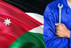 Jordanian Werktuigkundige in blauwe eenvormig houdt moersleutel tegen golvende de vlagachtergrond van Jordanië Gekruiste wapenste royalty-vrije stock foto