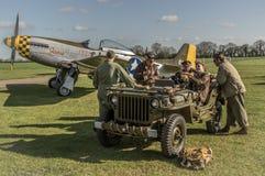 Jordbesättningen sitter i en jeep WW2 med en mustang P-51 i backgroen Royaltyfria Bilder