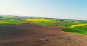 Jordbruk Surrsikt av den jordbruks- traktoren som besprutar fältet lager videofilmer