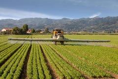 Jordbruk traktor som besprutar bekämpningsmedel på fältlantgård Arkivfoto
