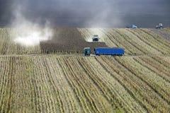 Jordbruks- arbeten i fältet Sammanslutningar, lastbilar och traktor Royaltyfri Bild