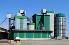 Jordbruks- byggnad för grön färg med kornsilor och uttorkningtorn Fotografering för Bildbyråer