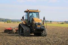 Jordbruks- crawlsimmaretraktor för utmanare på fält i höst Arkivbild