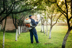 Jordbruks- detaljer - bonde som besprutar bekämpningsmedel och vikter för lokala växtbehandlingar royaltyfria foton