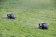 Jordbruks- fältarbete, två traktorer som rensar fältet Arkivfoton