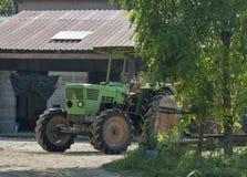 Jordbruks- lantgård och den gamla gröna traktoren Royaltyfri Bild